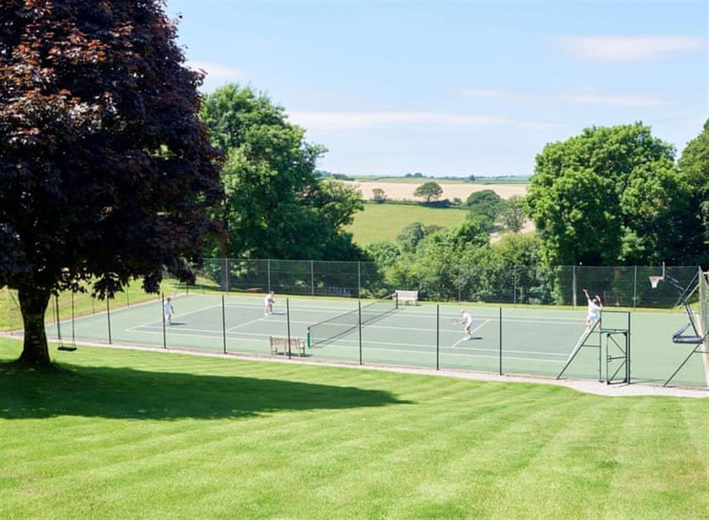 View over the lawned gardens to the tennis court at Meavy Cottage,