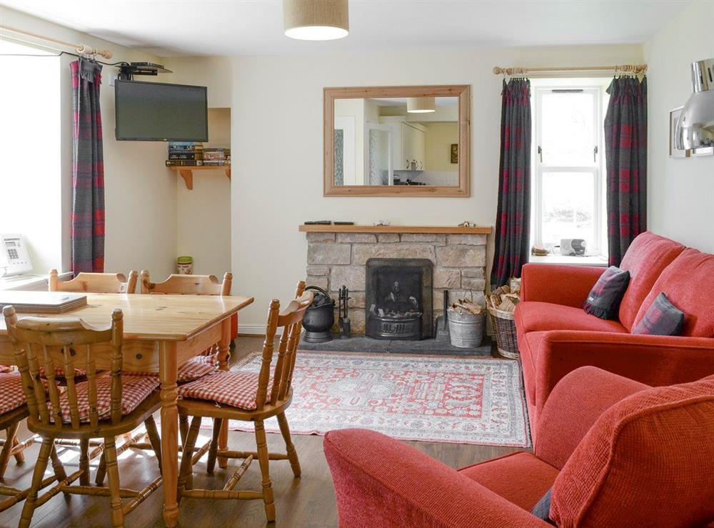 Spacious living room with convenient dining table at Rowan Cottage,