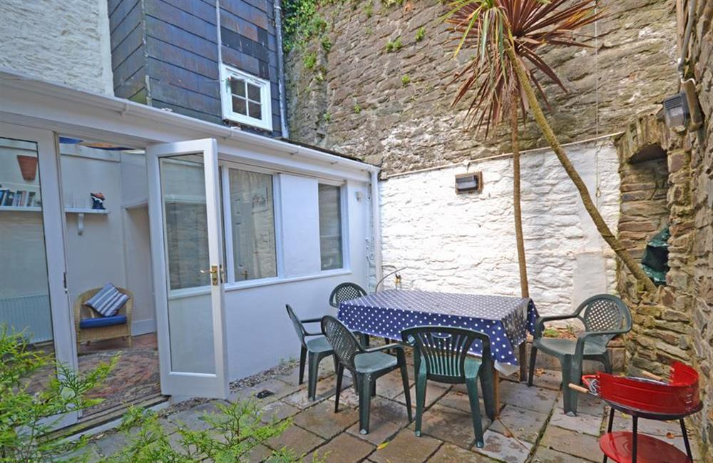 The enclosed courtyard garden with table, chairs and barbecue at Grants Cottage, Dartmouth