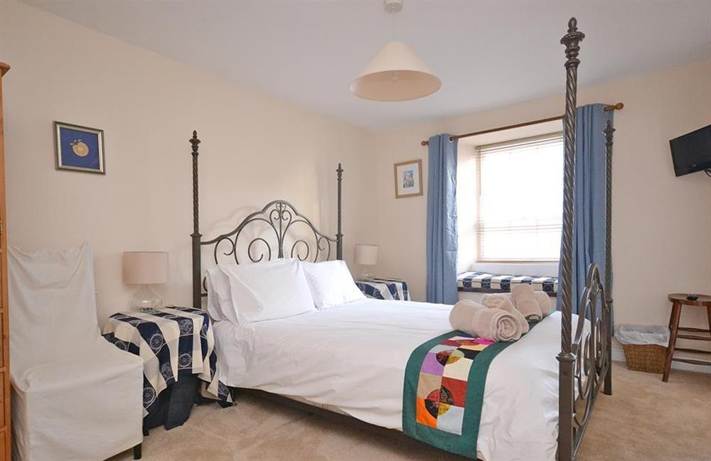 The master bedroom with decorative four poster bed and en suite at Grants Cottage, Dartmouth