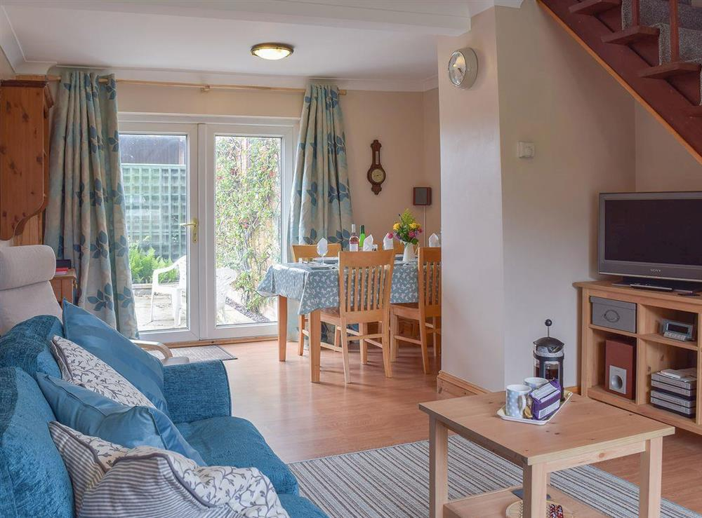 Living room/dining room with patio doors to garden at Grebe Cottage in West Somerton, near Winterton-on-Sea, Norfolk, England