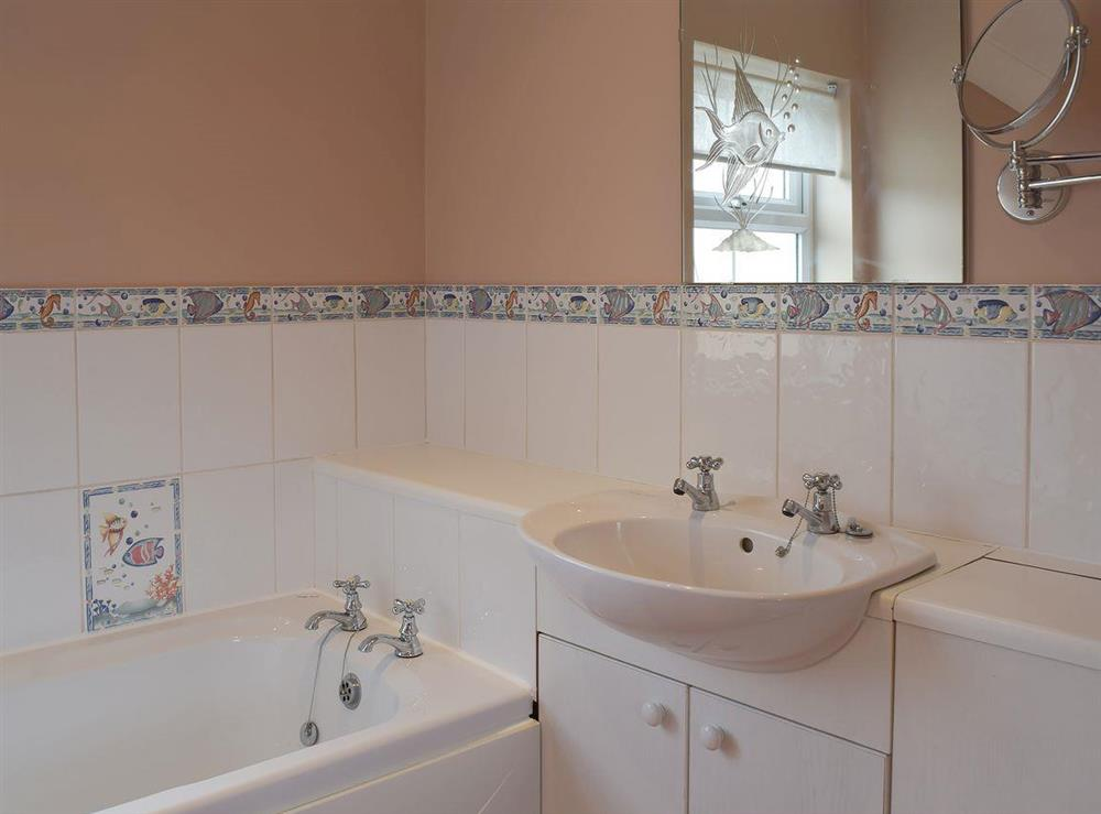 Part-tiled en-suite featuring a bath at Grebe Cottage in West Somerton, near Winterton-on-Sea, Norfolk, England