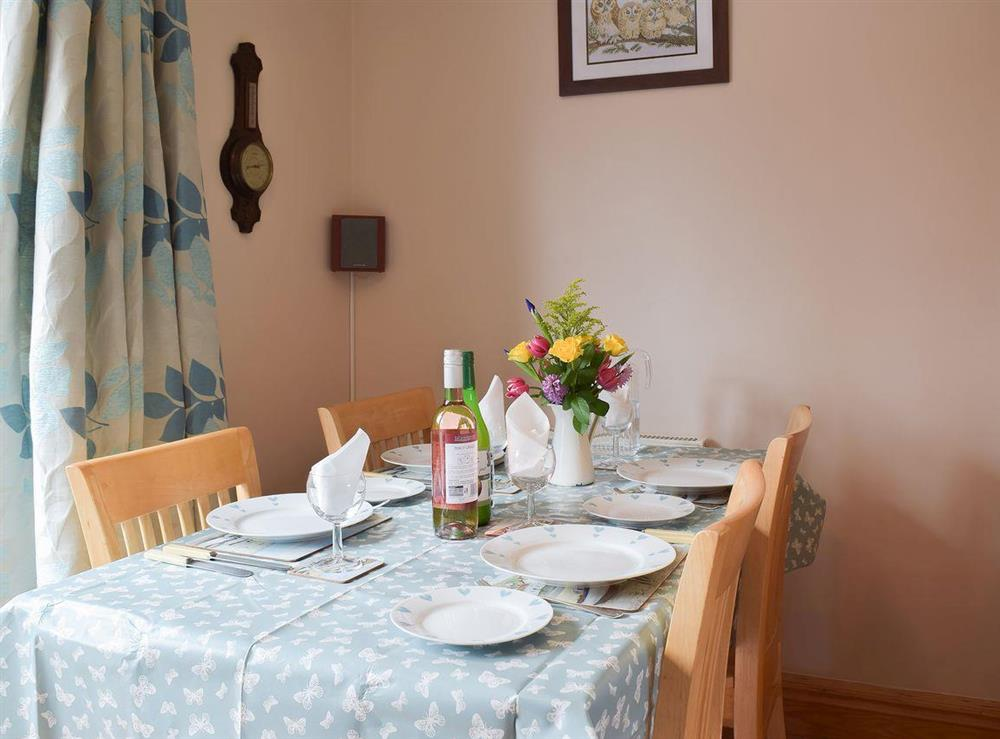 Sunny dining table next to the patio doors at Grebe Cottage in West Somerton, near Winterton-on-Sea, Norfolk, England