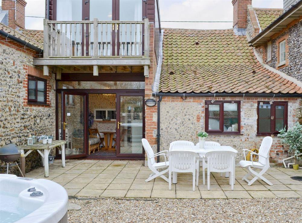 Attractive rear courtyard with hot tub and sitting-out-area at Gull Cottage in Morston, near Wells-next-the-Sea, Norfolk