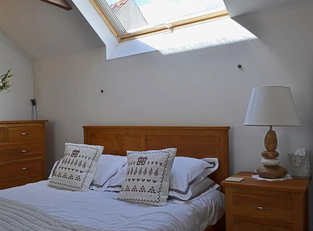 Exposed beams and sloping ceiling add to the romantic feel of the double bedroom at Half Penny Cottage in Docking, near Hunstanton, Norfolk