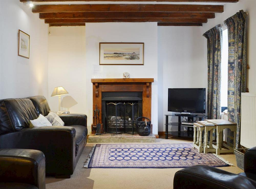 The beamed living room has a splendid open fireplace at Half Penny Cottage in Docking, near Hunstanton, Norfolk