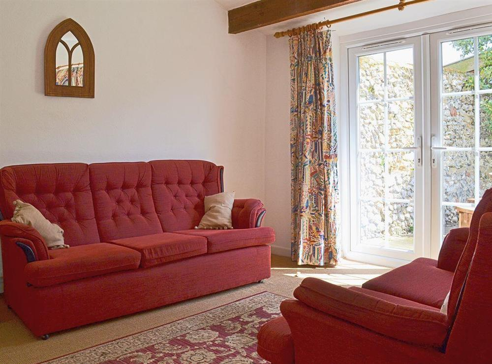 The garden room has French doors that open onto the patio and garden at Half Penny Cottage in Docking, near Hunstanton, Norfolk
