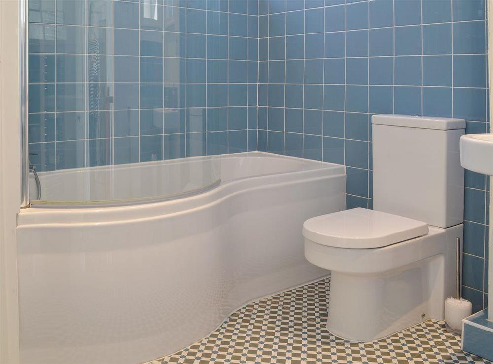 The house bathroom is fully tiled and has a feature shower over the bath at Half Penny Cottage in Docking, near Hunstanton, Norfolk