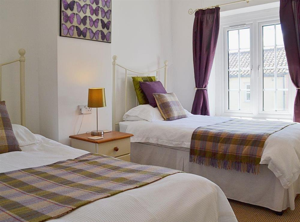 This twin bedroom has antique style single beds at Half Penny Cottage in Docking, near Hunstanton, Norfolk