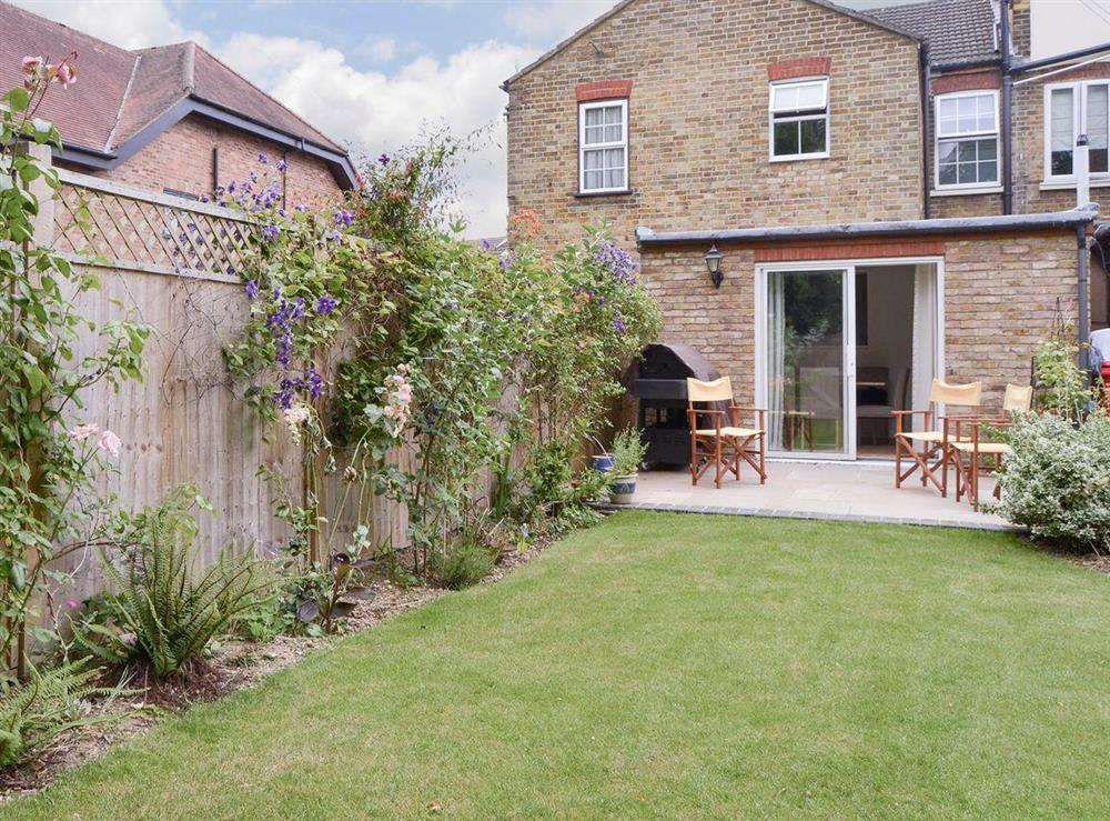 Garden area with paved patio to rear of holiday home at Harrison Barber Cottage in Colnbrook, near Windsor, Berkshire