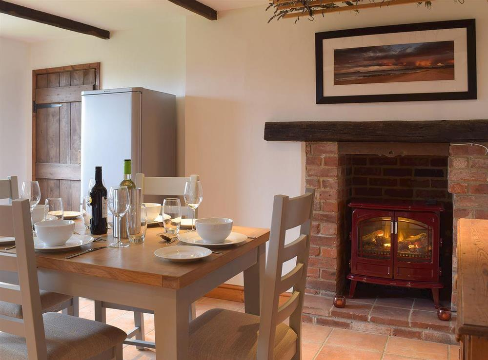 Cosy dining area with traditional fireplace and contemporary electric woodburner at Heathcote Cottage in Hickling, near Wroxham, Norfolk