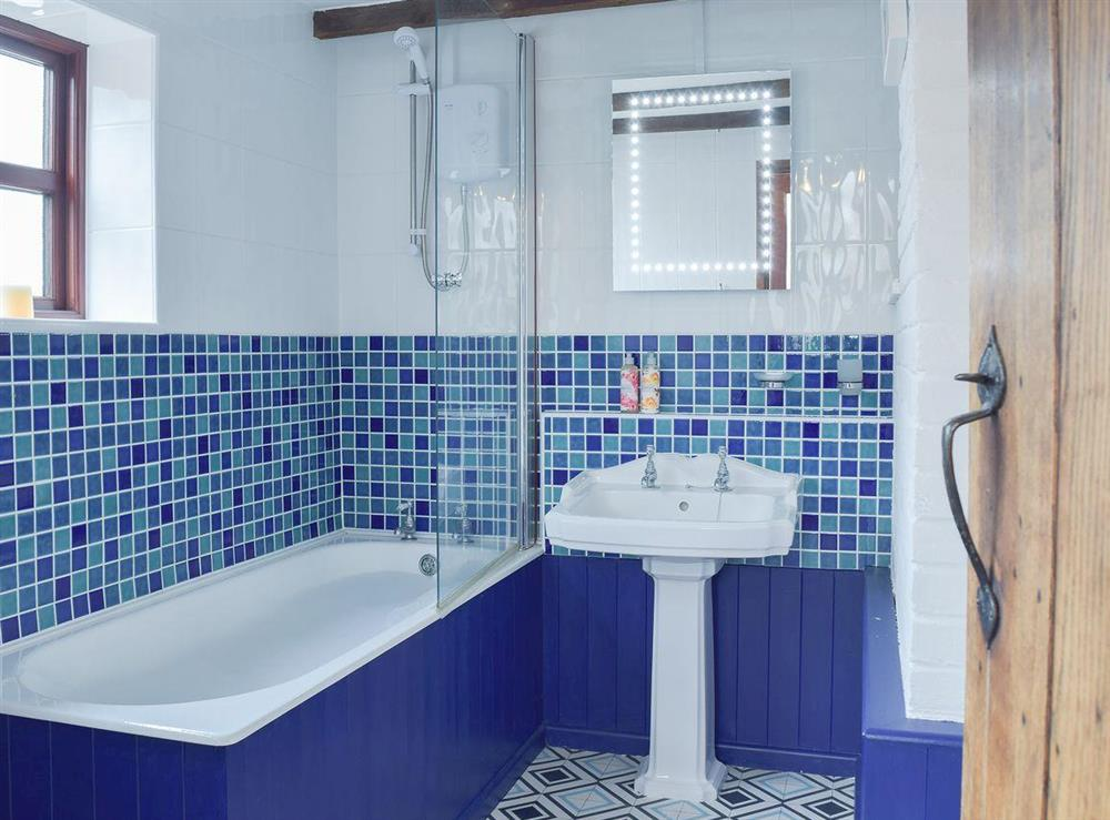 Tiled bathroom with shower over bath at Heathcote Cottage in Hickling, near Wroxham, Norfolk