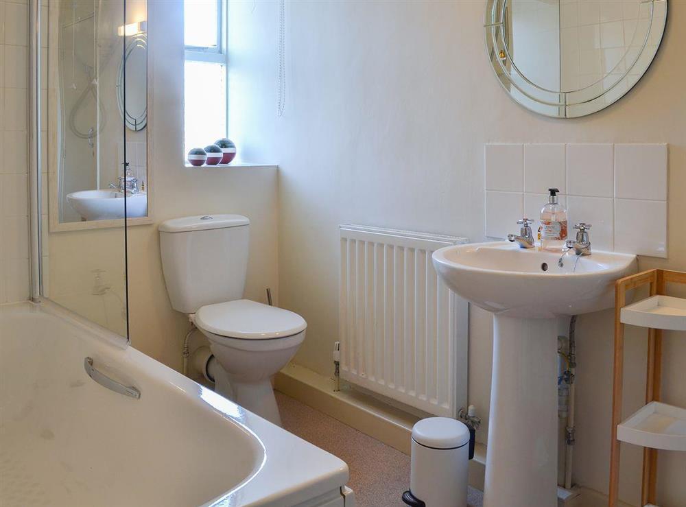 Pleasant bathroom with shower over bath at Daron,
