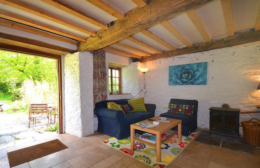 The sitting room with oak door opening onto a sunny garden with table and chairs at Higher Cotterbury Cottage, Blackawton