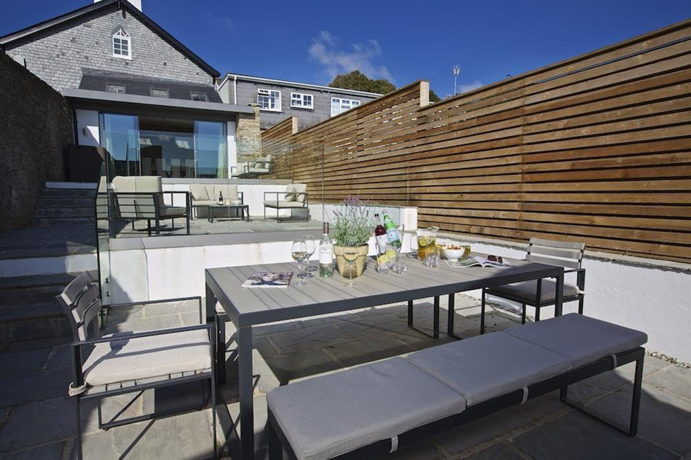 Private three-tiered terrace with tables and chairs at each level at Hillfield Farmhouse in , Hillfield, Dartmouth