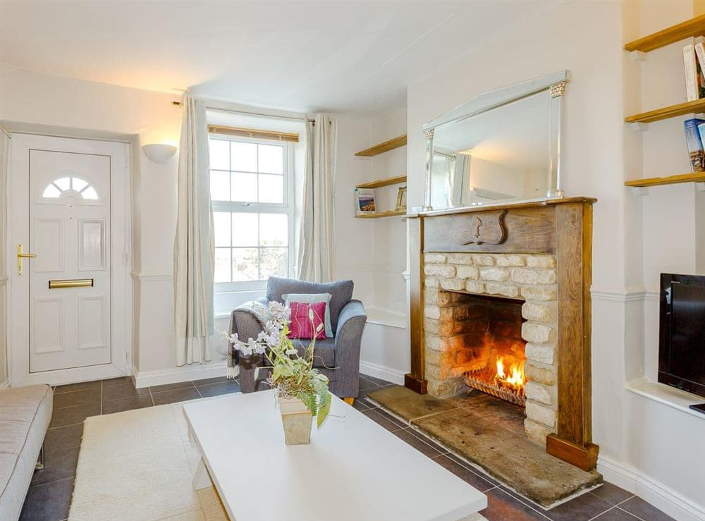 Well presented living room with an open fire at Jacks Cottage in Easton On The Hill, near Stamford, Northamptonshire