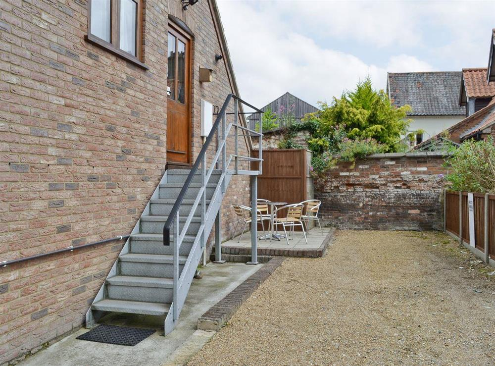 Gravelled courtyard and entrance to holiday home via steps at Kingfisher in Wells-next-the-Sea, Norfolk