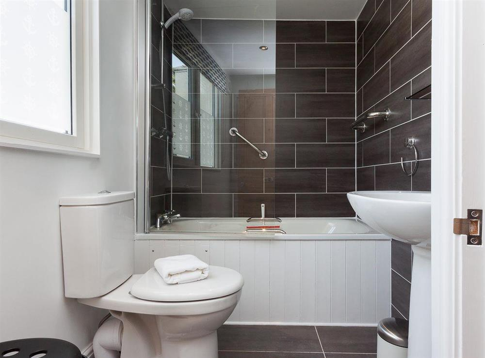 Beautifully tiled bathroom with shower over the bath at Kitkat Cottage in Dartmouth, Devon