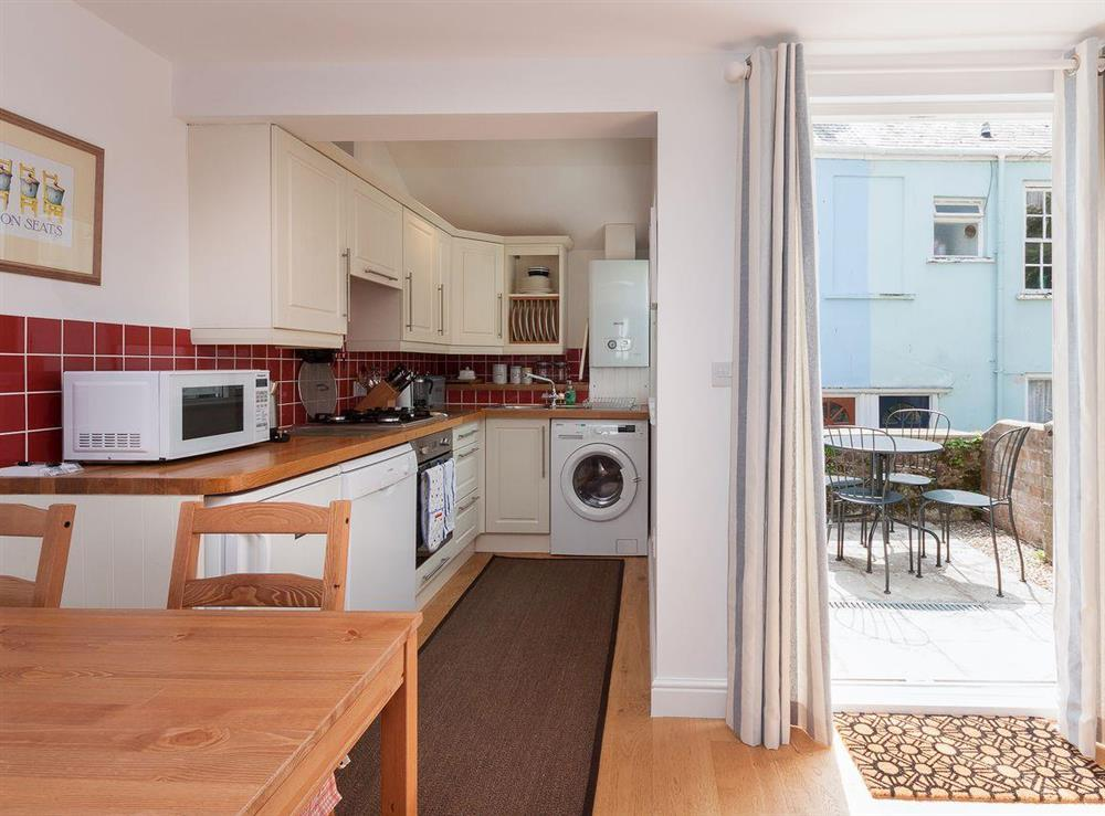 Modest dining area and kitchen with access to balcony at Kitkat Cottage in Dartmouth, Devon