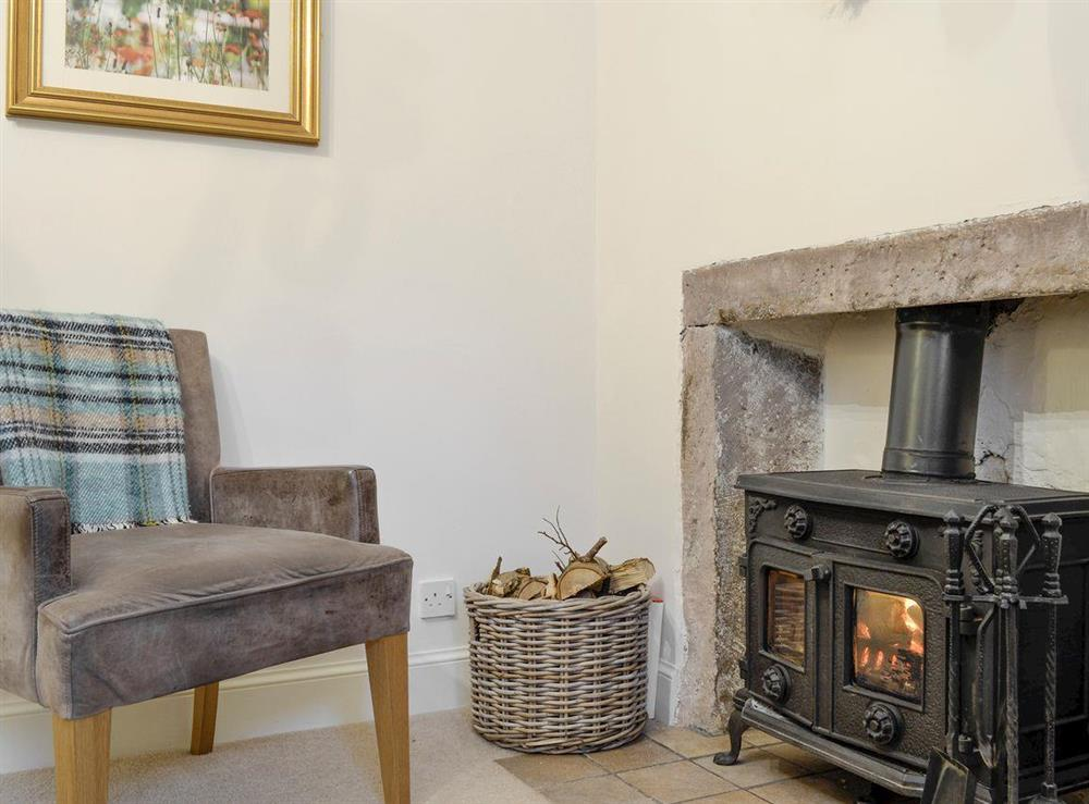 Additional seating area and wood burner within kitchen at Lilac Bank Cottage in Crosshill, near Maybole, Ayrshire
