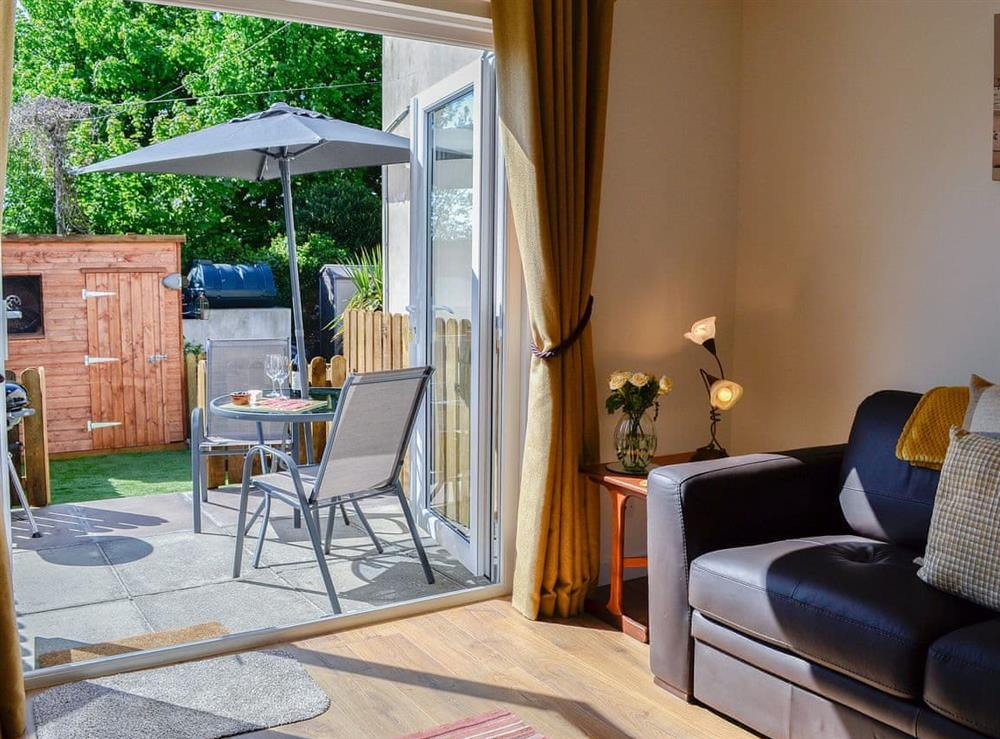 French doors open from the living room to the paved patio and garden at Little Cottage in Wigtown, Dumfries and Galloway, Wigtownshire