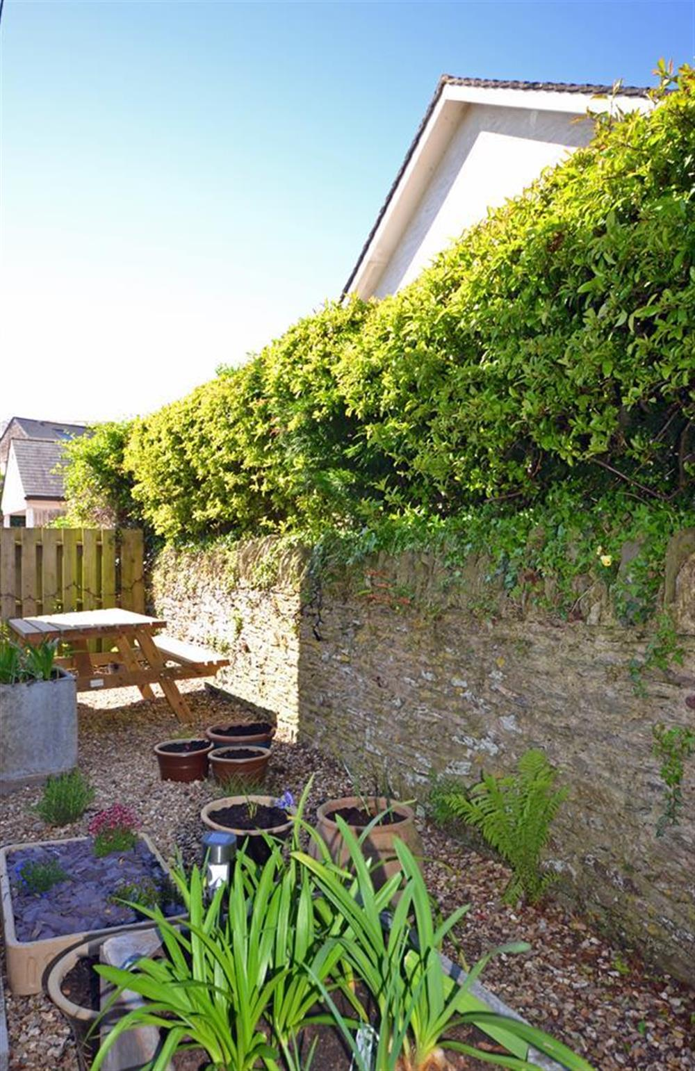 The small enclosed garden with picnic bench at the rear of the property at Lydiard Cottage, Loddiswell