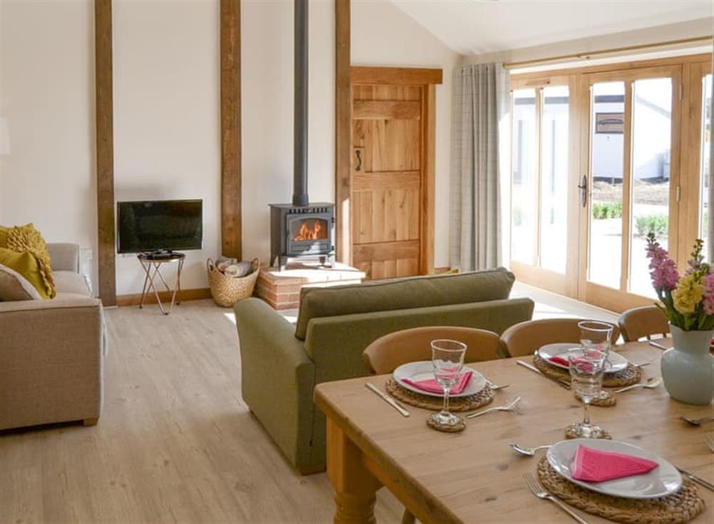 Stylish open-plan living space with French doors to patio area at Berts Barn,