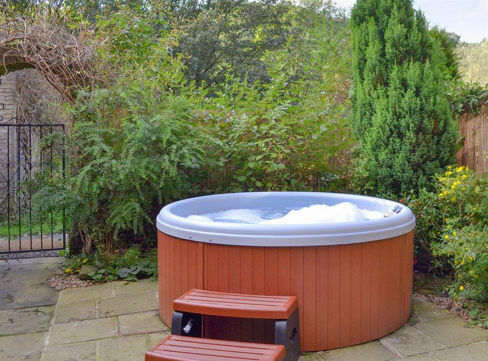 Luxurious hot tub in enclosed courtyard at Mallard Cottage in Holmfirth, West Yorkshire