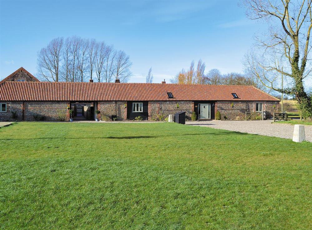 Exterior, traditional Norfolk brick and flint barns, with large lawned garden at Owls Roost,