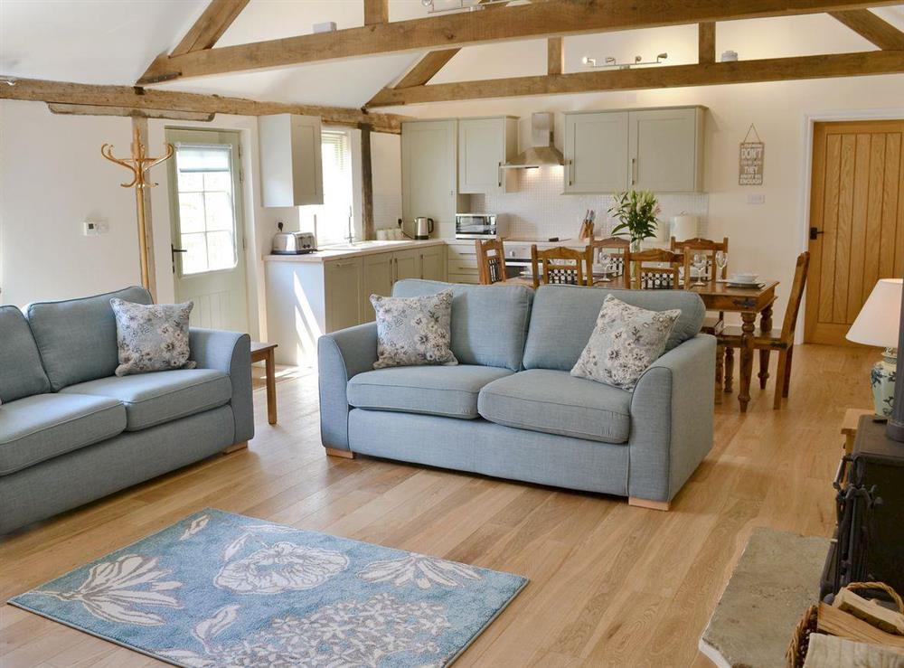 Open plan living space boasting character features, oak flooring & woodburner at Squirrels Drey,