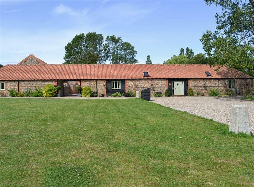 Exterior, traditional Norfolk brick and flint barns, with large lawned garden at Stags Rest,