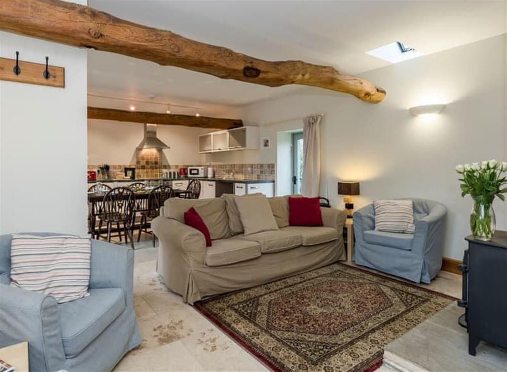 Open plan living space with beams and marble floor at The Piggery,