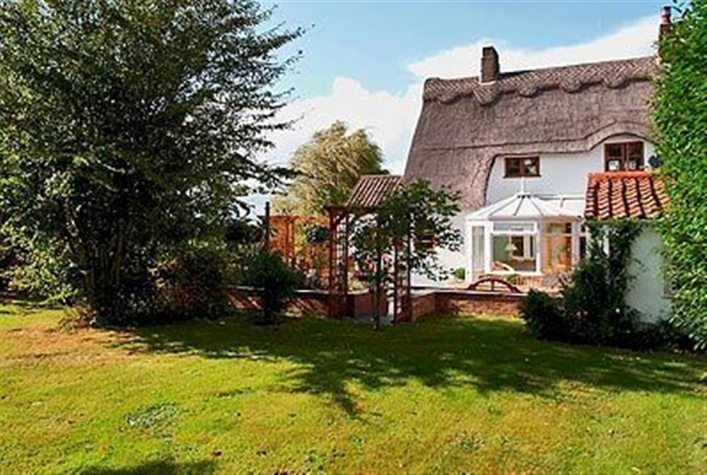 The lawned garden and thatched roof at May Cottage in Bacton, Nr North Walsham, Norfolk., Great Britain