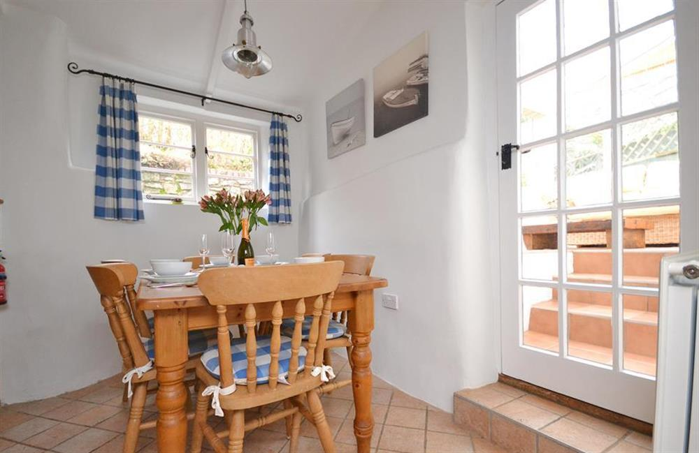 The dining area with steps leading into the conservatory at Meadow View Cottage, Dittisham