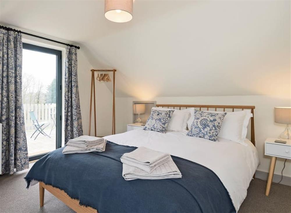 Tastefully furnished double bedroom with French door leading to balcony at Meadow View in North Walsham, Norfolk