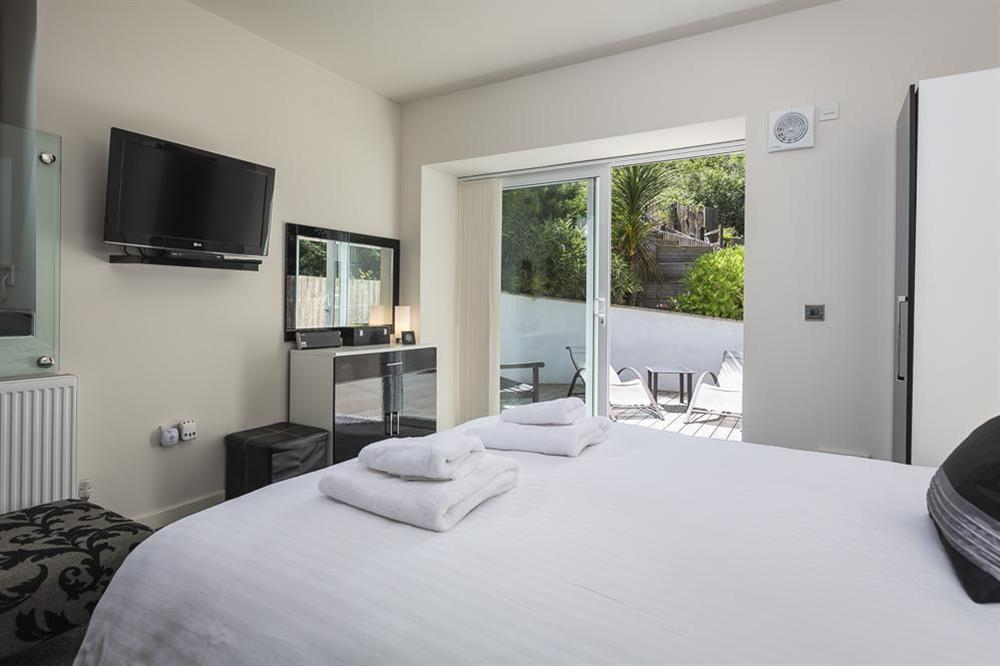 En suite master bedroom (at lower ground floor level) with King-size bed at Mill Grange in , Dartmouth