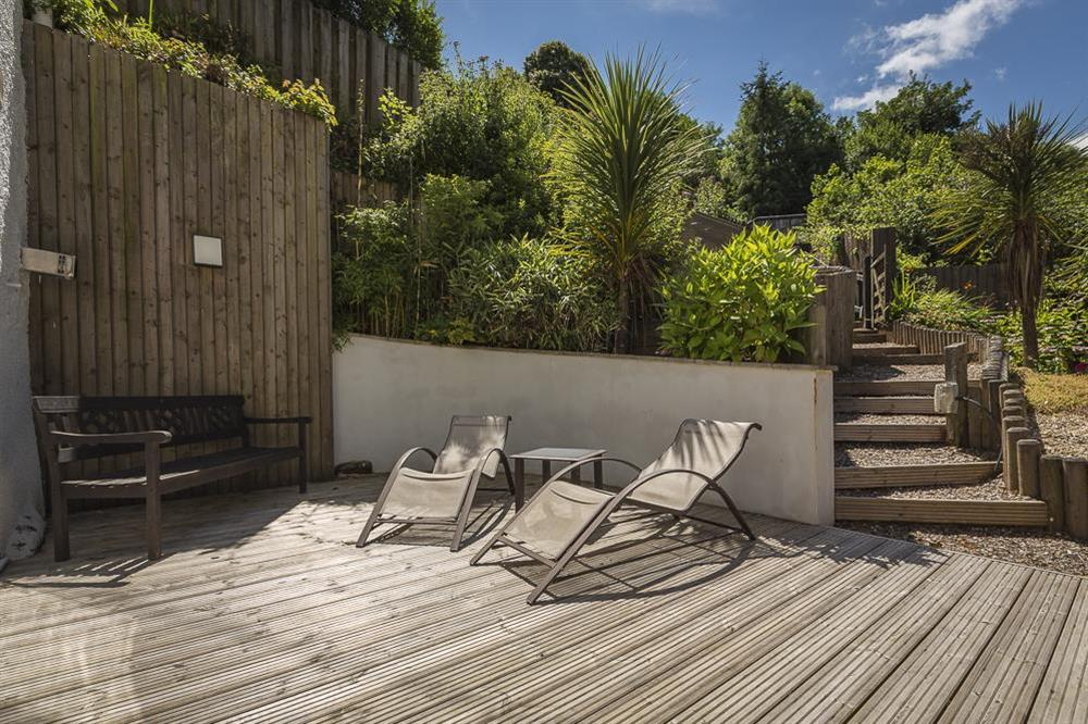 French doors lead to a private decking area with loungers and seating at Mill Grange in , Dartmouth