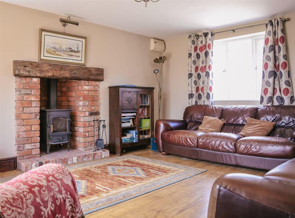 Spacious living room with wood burning stove at Millers House,