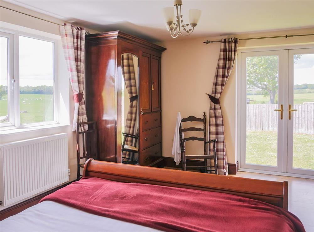 The master bedroom commands panoramic rural views and French door access to the garden at Millers House,