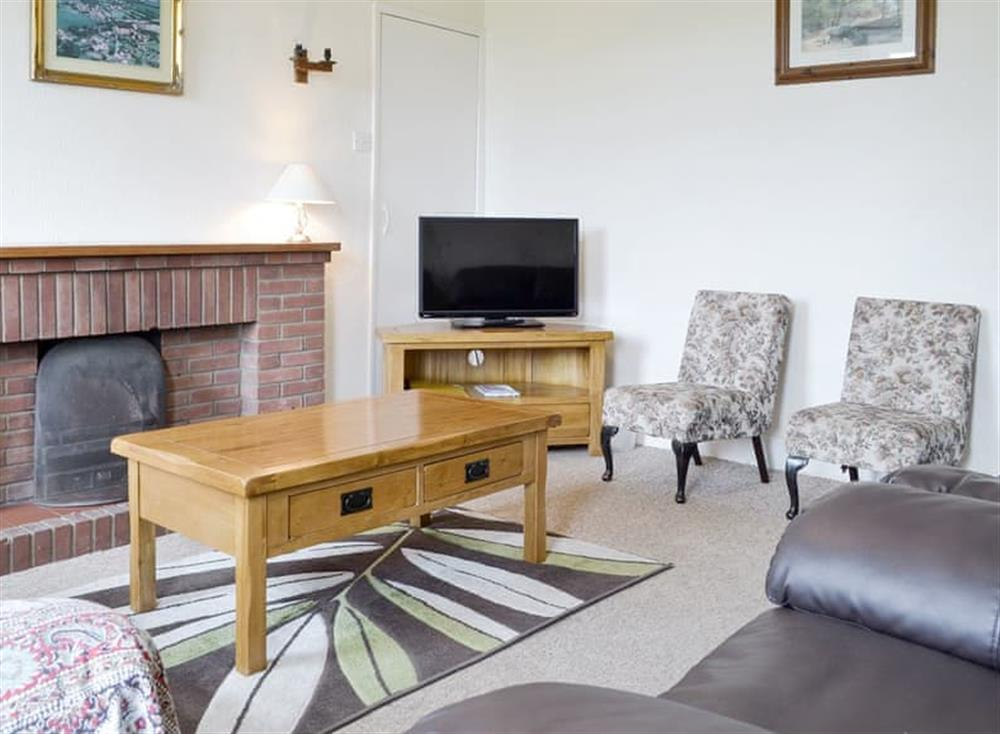 Welcoming living room with open fire at Moor Farm Cottage,