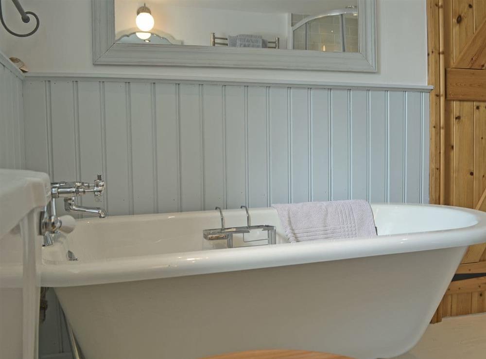 Bathroom featuring an impressive roll-top bath, shower cubicle and toilet at Mur Llwyd in Rhoshirwaun, near Pwllheli, Gwynedd