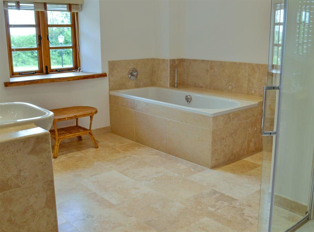 Bathroom with bath, shower cubicle, toilet, bidet, heated towel rail and tiled floor at New Inn Farmhouse in Marnhull, near Shaftesbury, Dorset