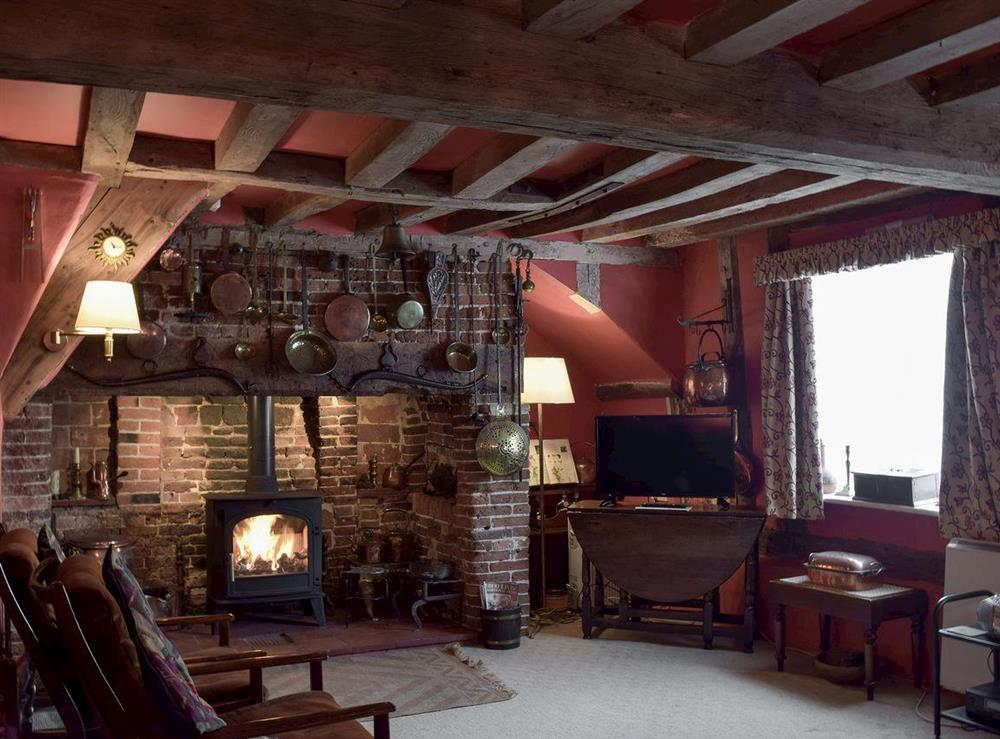 Cosy living room with exposed beams & wood burner at Old Maltsters Arms Cottage in Pulham St Mary, near Diss, Norfolk
