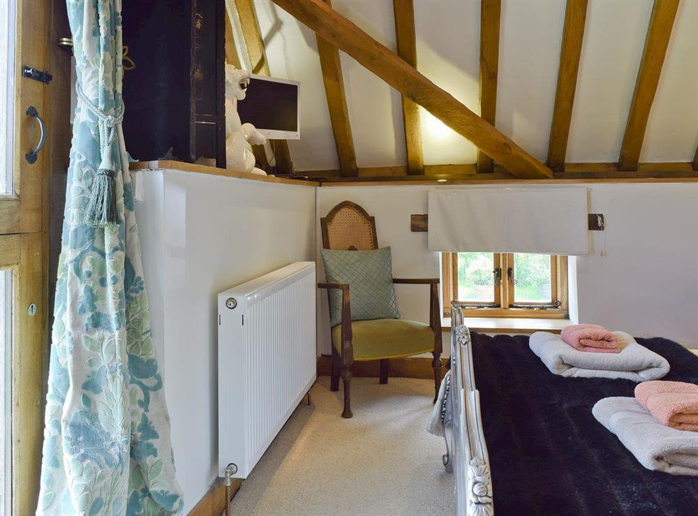 Wall mounted TV in bedroom at Falstaff Cottage,