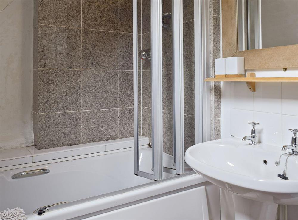 Bathroom with shower over bath at Lovers Cottage,