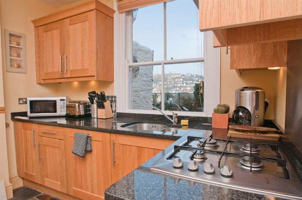 Kitchen with view of patio and Kingswear at Onedin House in 11 Crowthers Hill, Dartmouth