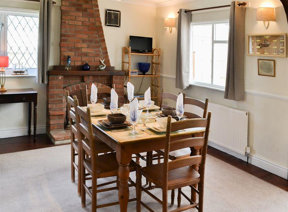 Dining room with feature fireplace and exposed woodwork at Park End in Walcott, near Stalham, Norfolk