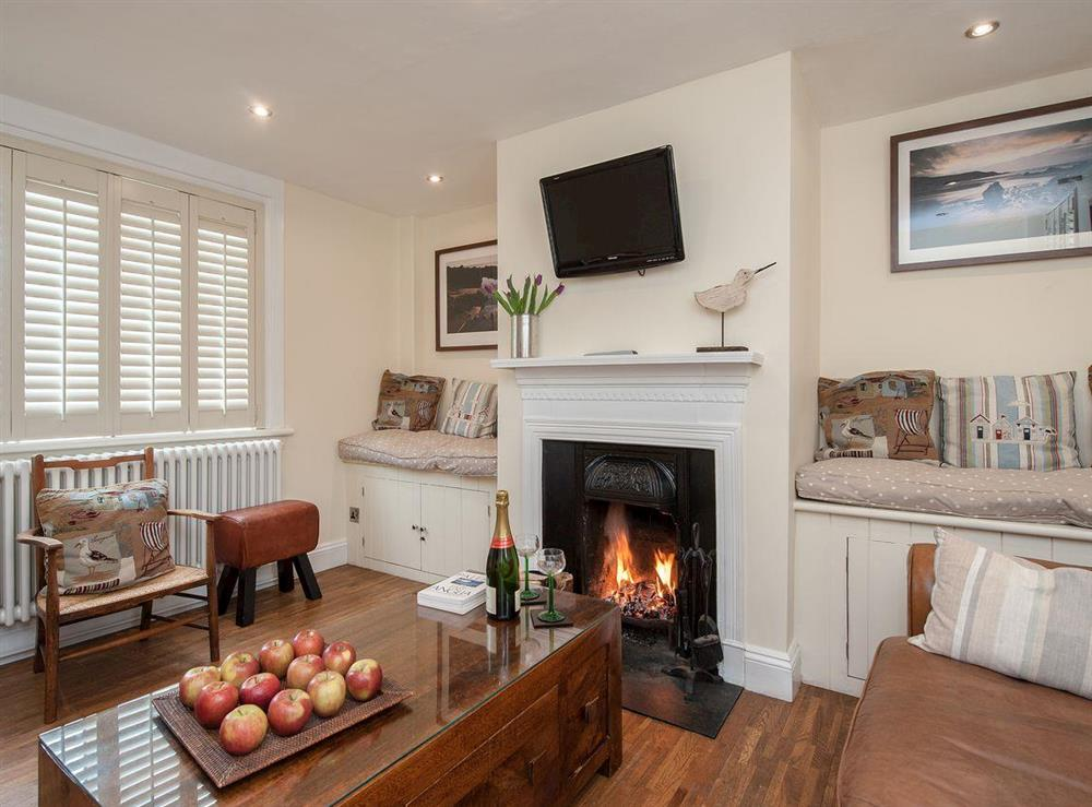 Cosy living room with open fire & wooden floor at Pebble Cottage in Aldeburgh, Suffolk, England