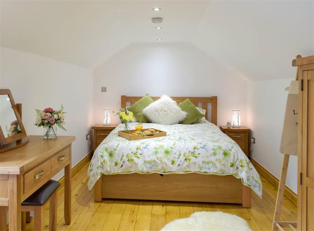 Relaxing bedroom with kingsize bed and wooden floor at Snowdrop Cottage,