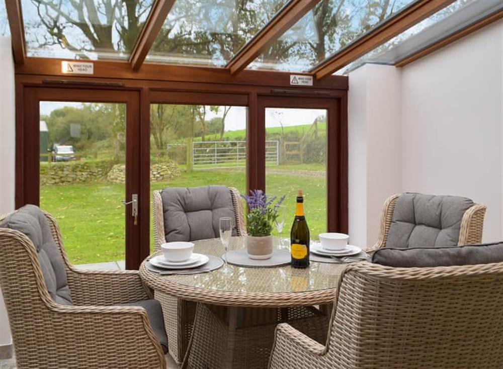Sun room/dining area with patio doors leading to garden (photo 2) at Snowdrop Cottage,